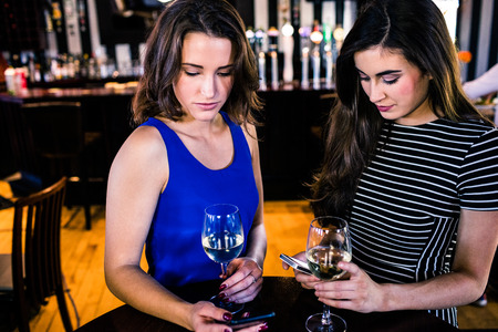 Friends texting and having a glass of wine in a bar