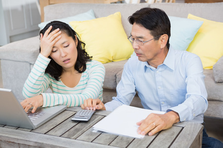 Worried couple checking bills in the living room