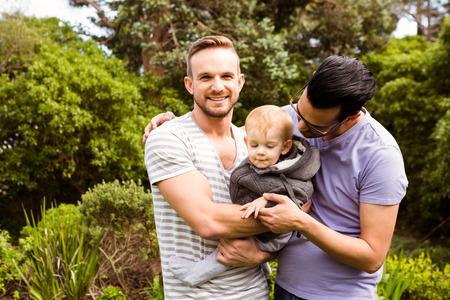 Photo pour Smiling gay couple with child in garden - image libre de droit