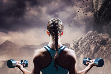 Rear view of braided hair woman lifting dumbbells against rock crashing down from cliff