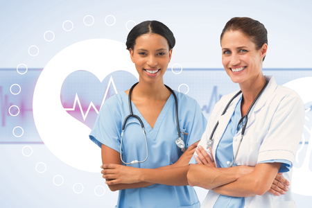 Portrait of smiling female doctors standing arms crossed against medical background with green ecg line