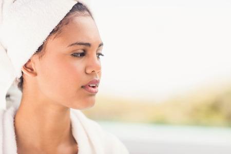 Peaceful brunette wearing white towel looking away
