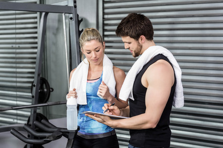 Smiling fit couple taking notes at crossfit gym