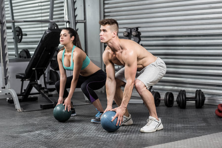 Fit couple doing ball exercise at crossfit gym