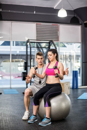 Male trainer assisting woman lifting dumbbells at crossfit gym