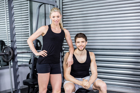 Portrait of smiling fit couple at crossfit gym