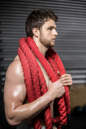 Man with rope around his neck at crossfit gym