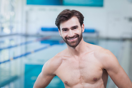 Handsome shirtless man standing with hands on hips at the pool