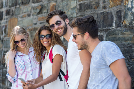 Hip friends looking at smartphone leaning against wall
