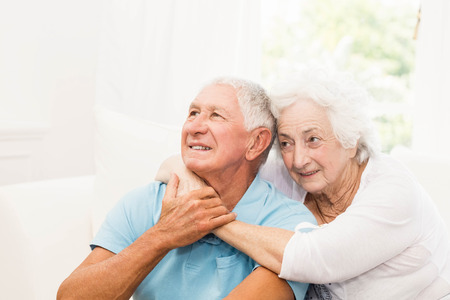 Cute senior couple hugging on sofa