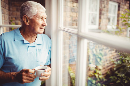 Photo for Senior man holding cup and looking out of the window at home - Royalty Free Image