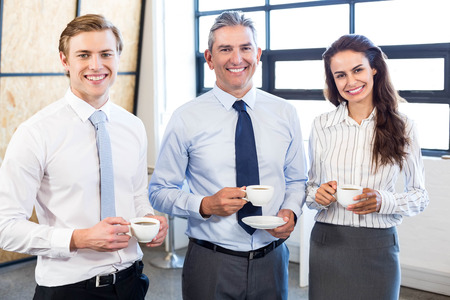 Portrait of businesspeople together and smiling in office during breaktime