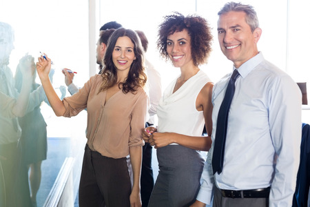 Portrait of businesspeople smiling while writing on white board in office