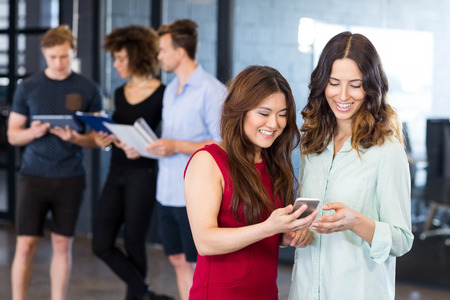 Women looking at smartphone and having discussion while colleagues standing behind in office