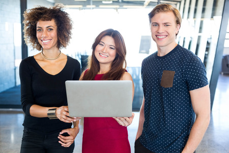 Portrait of colleagues holding laptop and smiling in office
