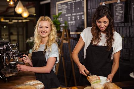 Photo pour Pretty waitresses behind the counter working at the coffee shop - image libre de droit