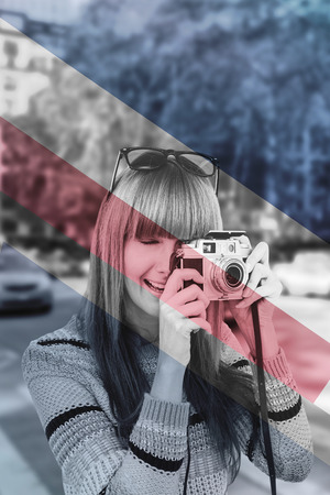 Smiling hipster woman taking pictures with a retro camera against colored background