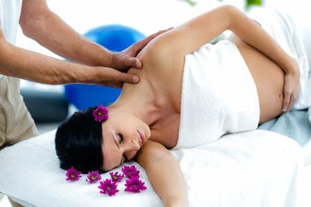Photo pour Pregnant woman receiving a back massage from masseur at health spa - image libre de droit