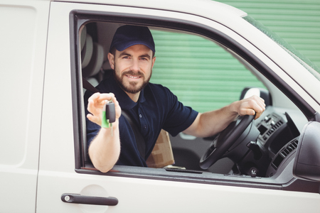 Photo for Delivery man sitting in his van while holding keys - Royalty Free Image