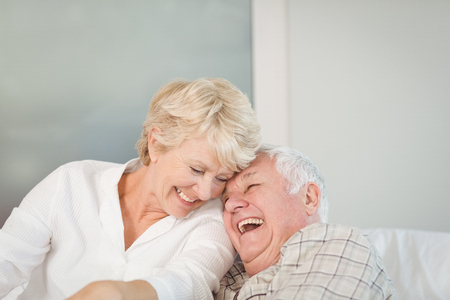 Photo pour Happy senior couple laughing in bed at home - image libre de droit