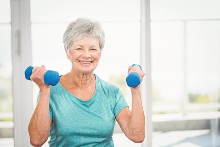 Photo pour Portrait of happy senior woman holding dumbbell at home - image libre de droit