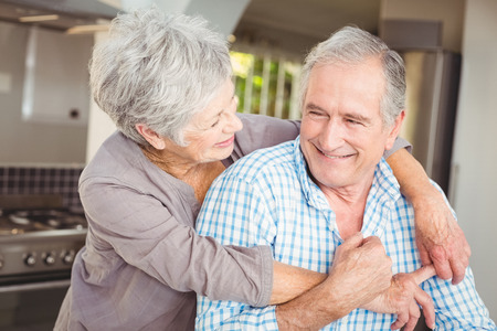 Cheerful senior couple embracing in kitchen at home