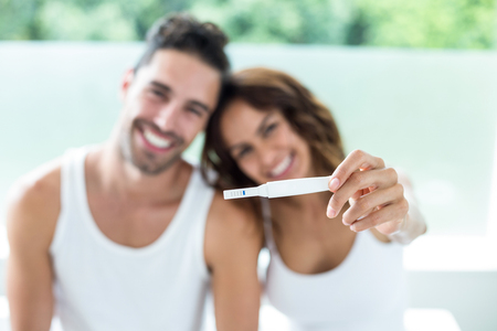 Photo for Portrait of happy couple showing pregnancy kit - Royalty Free Image