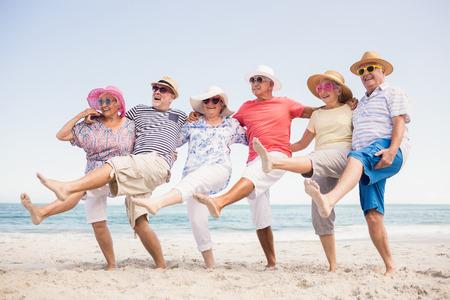 Photo pour Happy senior friends dancing on the beach - image libre de droit