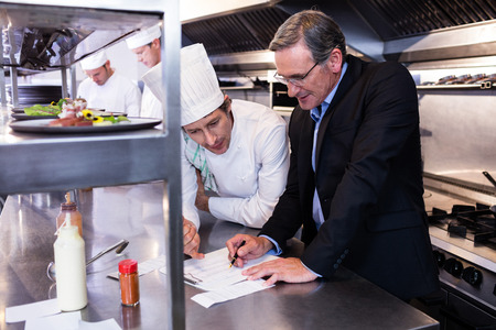 Foto de Male restaurant manager writing on clipboard while interacting to head chef in commercial kitchen - Imagen libre de derechos