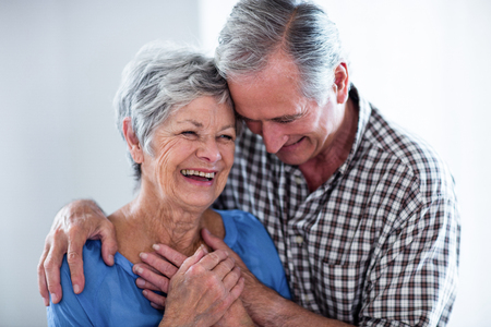 Happy senior couple smiling while embracing at home