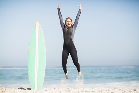 Photo pour Excited woman in wetsuit jumping next to her surfboard on the beach - image libre de droit