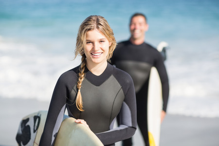 Photo pour Happy woman in wetsuit holding a surfboard on the beach on sunny day - image libre de droit