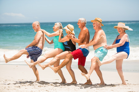 Seniors dancing in a row at the beach on a sunny day