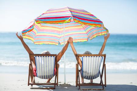 Photo pour Cute mature couple raising arms on deckchairs on the beach - image libre de droit