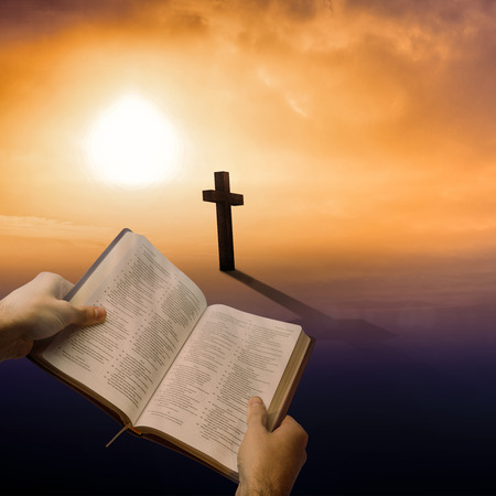 Man holding a holy bible against cross religion symbol shape over sunset sky