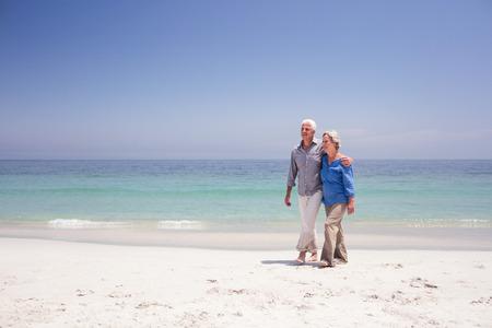Foto de Senior couple walking on the beach on a sunny day - Imagen libre de derechos