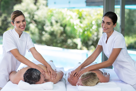 Relaxed young couple receiving a back massage from masseur in spa