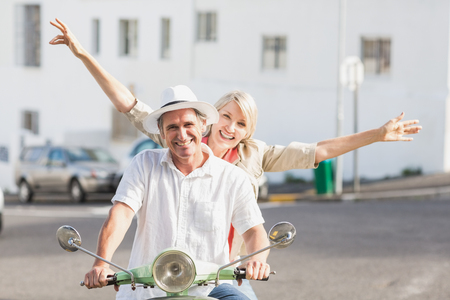 Portrait of happy couple riding motor scooter on street in city