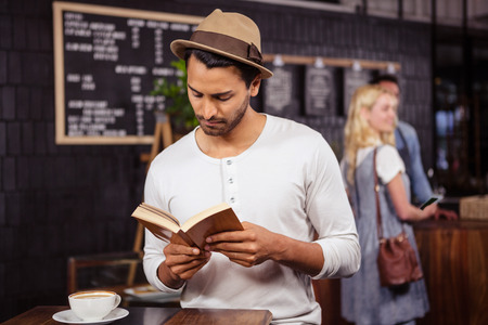 Man reading a book in a coffee shop