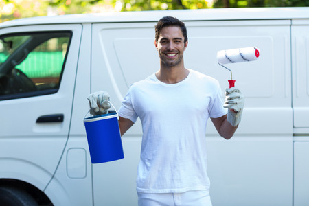 Portrait of happy painter standing with bucket and roller against van