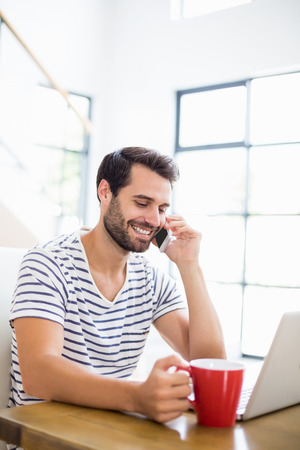 Man having coffee while talking on phone at home