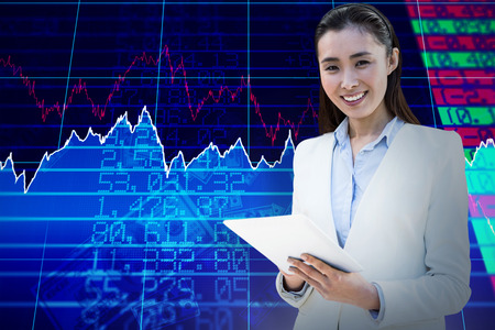 Smiling businesswoman writing on notepad against stocks and shares