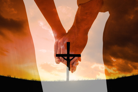 Photo pour Bride and groom holding hands close up against cross religion symbol shape over sunset sky - image libre de droit