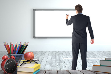 Businessman standing back to camera writing with marker against screen in modern white room