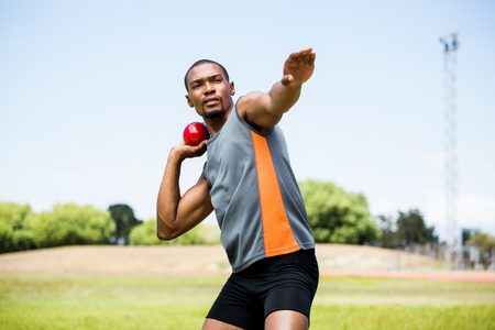 Male athlete about to throw shot put ball in stadium