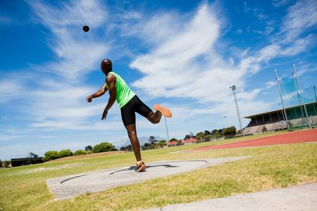 Male athlete throwing shot put ball in stadium