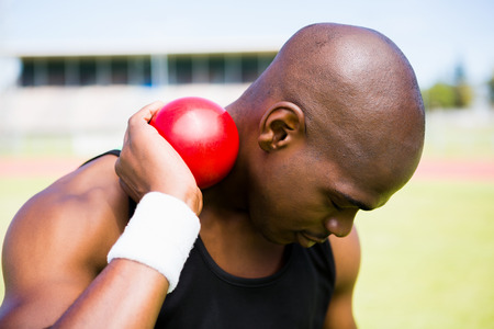 Male athlete holding shot put ball in stadium