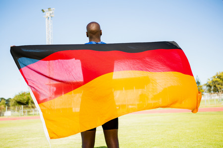Rear view of athlete posing with german flag after victory in stadium