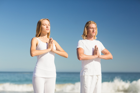 Man and woman performing yoga on beach