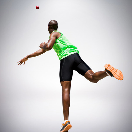 Rear view of sportsman throwing a shot against grey background
